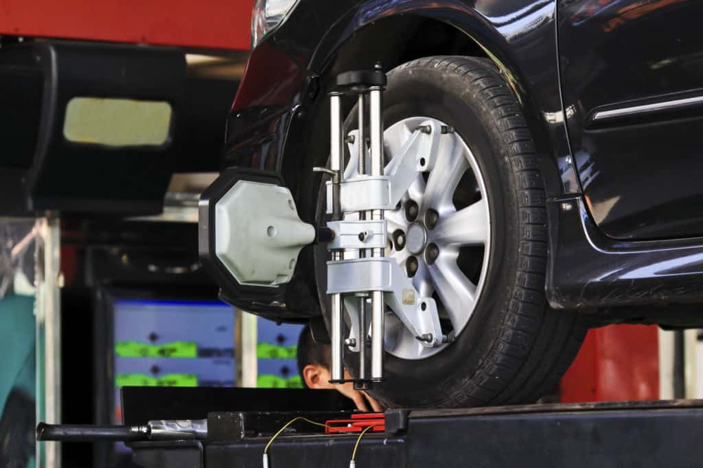 Car wheel fixed with computerized wheel alignment machine clamp.